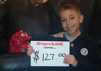 Child holding a sign that says how much they saved with DragonBank